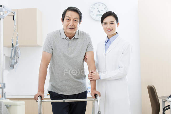 Chinese doctor helping patient with walker — Stock Photo