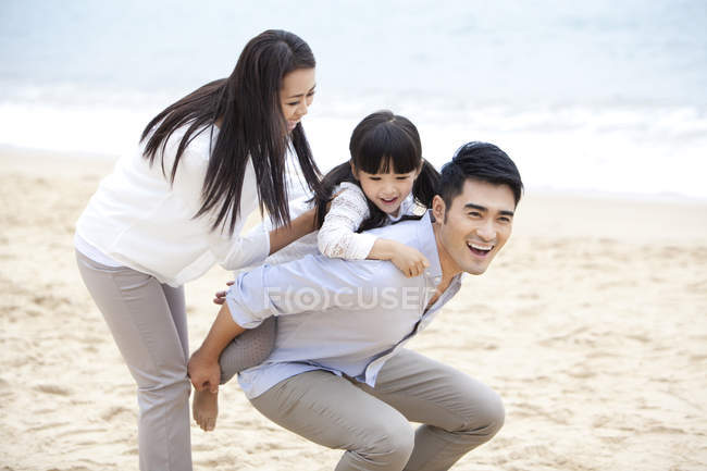 Chinese father giving daughter piggyback ride on beach with mother — Stock Photo