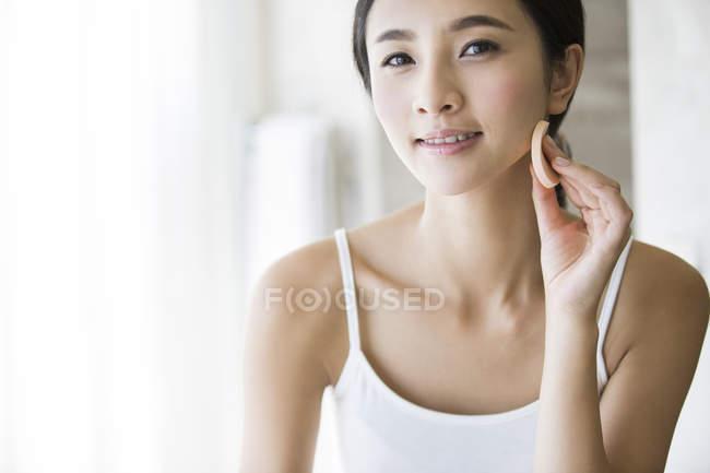 Joven chino aplicando polvo de la cara - foto de stock