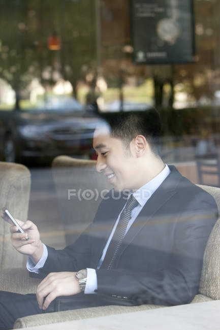 Uomo d'affari cinese utilizzando smartphone nella caffetteria — Foto stock