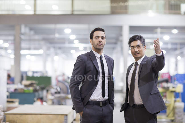 Businessmen standing at factory and looking in camera — Stock Photo