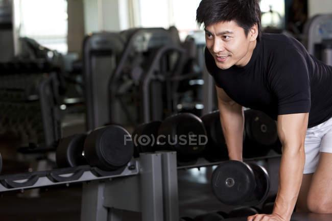 Китаец поднимает гантели в спортзале — стоковое фото