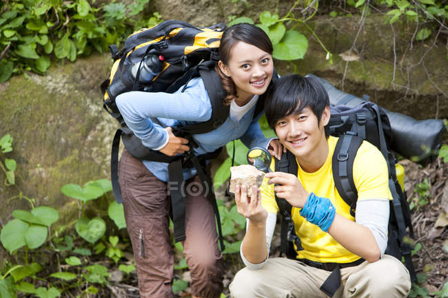 Chinese tourists studying fossil in forest — Stock Photo