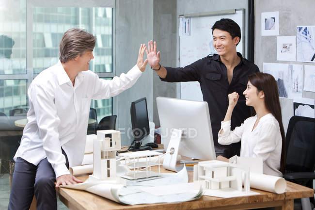Чоловічий архітекторів, роблячи high-five в офісі — стокове фото