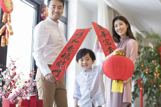 Cheerful family with decorative banners and lantern on Chinese New Year — Stock Photo