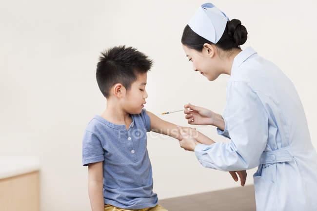 Enfermeira chinesa dando injeção menino — Fotografia de Stock