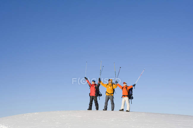 Chinese friends posing with ski poles in air — Stock Photo