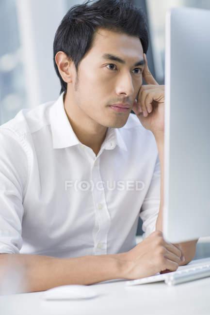 Empresário chinês pensivo usando computador no escritório — Fotografia de Stock