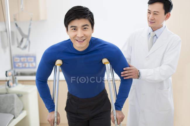 Китайський лікар, допомагаючи пацієнта з милицями — стокове фото