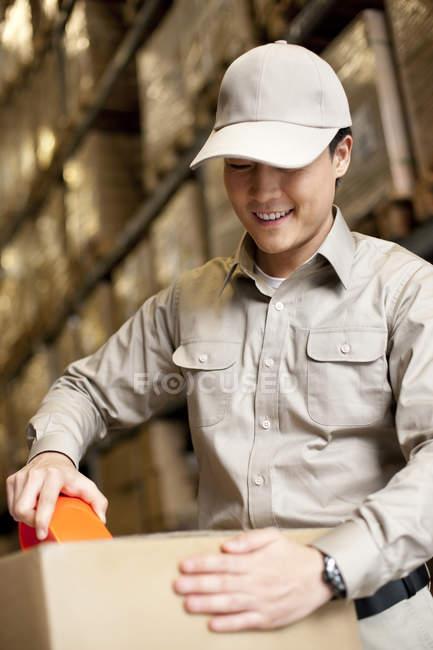 Masculino chinês armazém trabalhador embalagem caixa — Fotografia de Stock