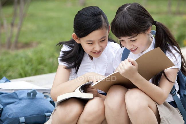 Schoolgirls sitting on steps and reading books — Stock Photo