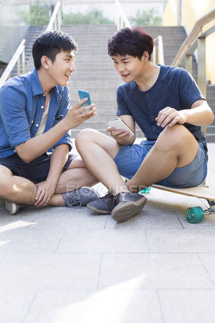 Chinese men sitting on skateboards and looking at smartphone — Stock Photo