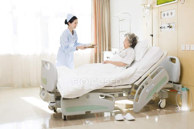 Enfermeira chinês, servindo de alimento para o paciente do sexo feminino sênior — Fotografia de Stock