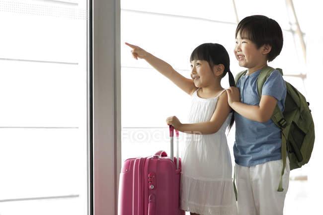 Chino chico y chica apuntando a la vista en el aeropuerto - foto de stock