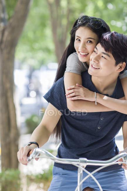 Китайська пара, їзда на велосипеді і, обнявши на вулиці — стокове фото