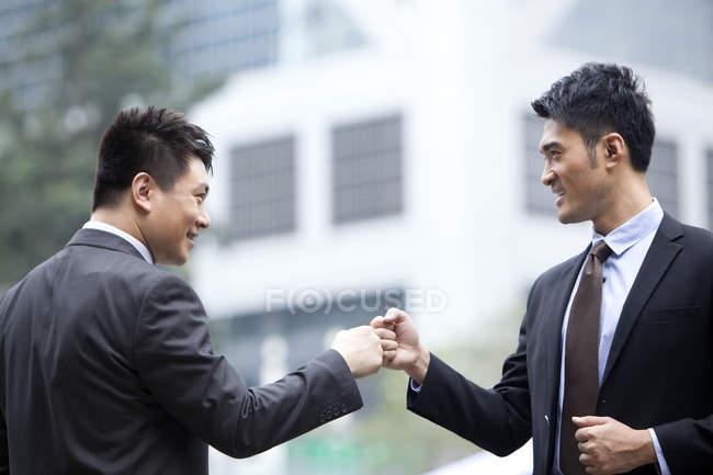 Animado de empresários chineses comemorando com punho galo na rua — Fotografia de Stock