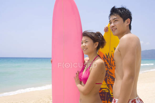 Young Chinese couple with surfboards looking at view — Stock Photo