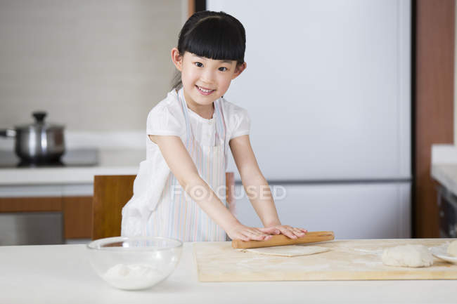 Chinese girl rolling dough on kitchen table and looking in camera — Stock Photo