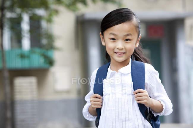 Chinesisches Schulmädchen mit Rucksack steht auf Straße — Stockfoto