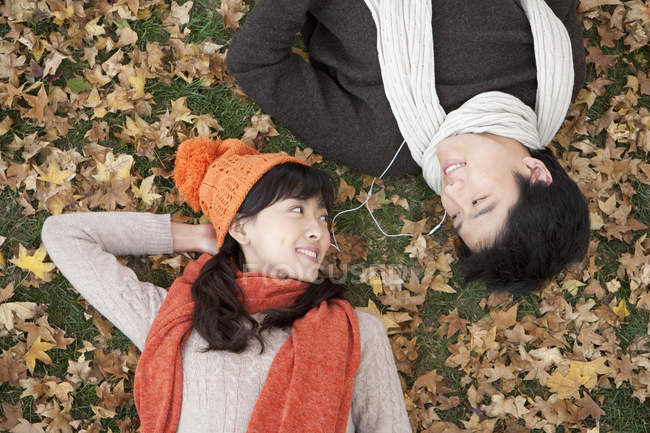 Chinese couple lying amongst maple leaves and sharing earphones — Stock Photo