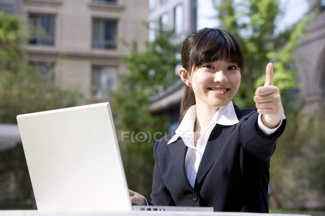 Китайский бизнес-леди с ноутбуком, дает большие пальцы на улице — стоковое фото