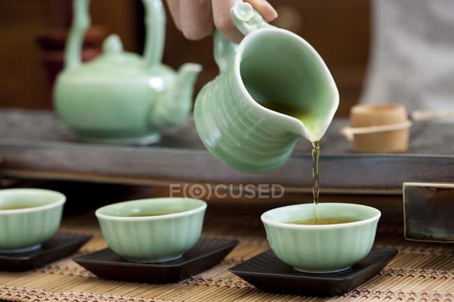 Femme main verser le thé dans les tasses à thé — Photo de stock