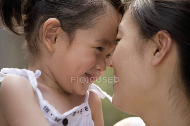 Chinese mother and daughter rubbing noses, close-up — Stock Photo