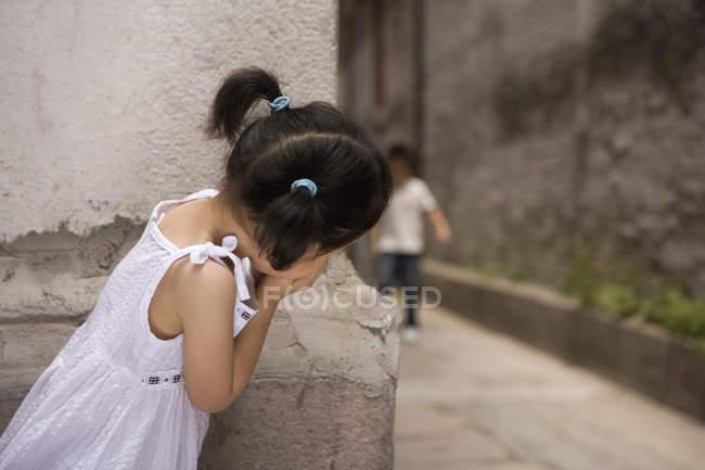 Menina espiando atrás de canto enquanto estiver jogando esconde e procurar — Fotografia de Stock