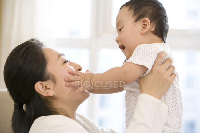 Chinese woman lifting baby boy with arms outstretched — Stock Photo
