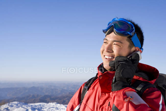 Chinese man in ski gear talking on mobile phone — Stock Photo