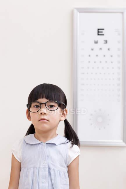 Retrato de menina chinesa com óculos na sala de optometria — Fotografia de Stock