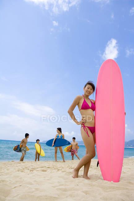 Китайська жінка, що стояла з дошки для серфінгу та друзями у фоновому режимі — стокове фото