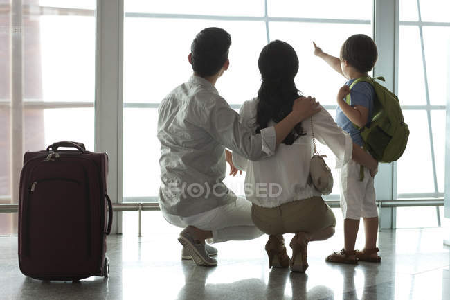 Chinese family pointing at view at airport — Stock Photo