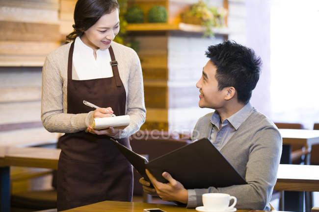 China camarera teniendo orden de hombre en cafetería - foto de stock
