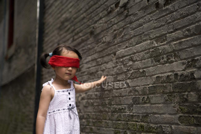 Китаянка с повязкой на глазах играет в прятки в переулке — стоковое фото