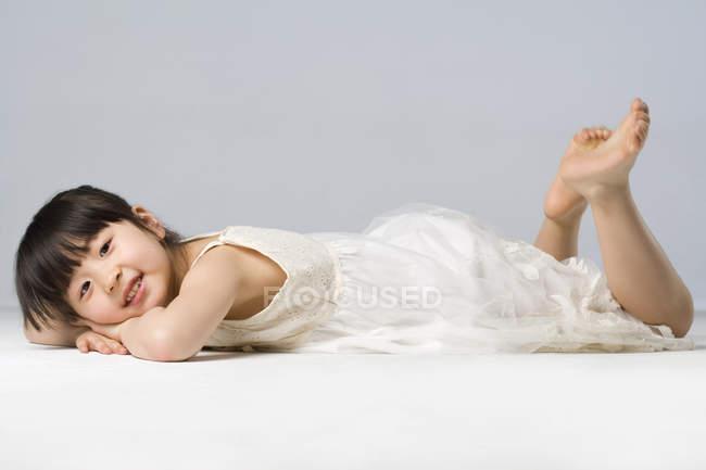 Kleines chinesisches Mädchen liegt vorne auf grauem Hintergrund — Stockfoto