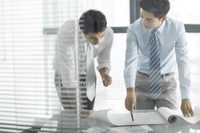Uomini d'affari cinesi discutono del progetto alla scrivania in ufficio — Foto stock