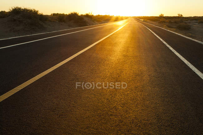 Road going through wilderness area in glowing setting sun, China — Stock Photo