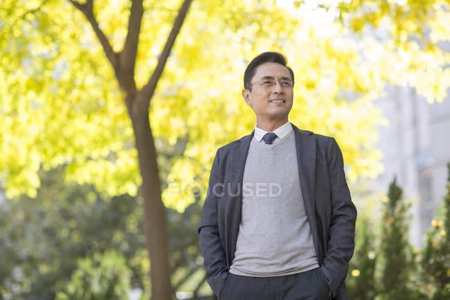Китайський бізнесмен, відпочиваючи, дивлячись на вигляд в парку — стокове фото