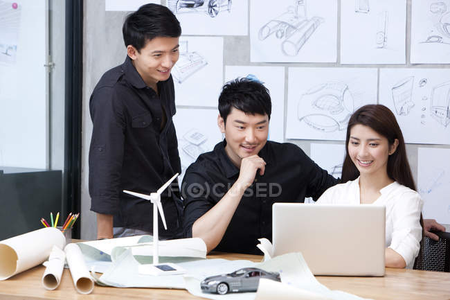 Team of designers working with laptop in office — Stock Photo