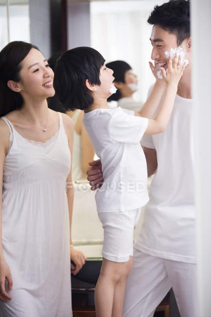 Chinesischen Vater und Sohn im Badezimmer mit Rasierschaum am Kinn ...
