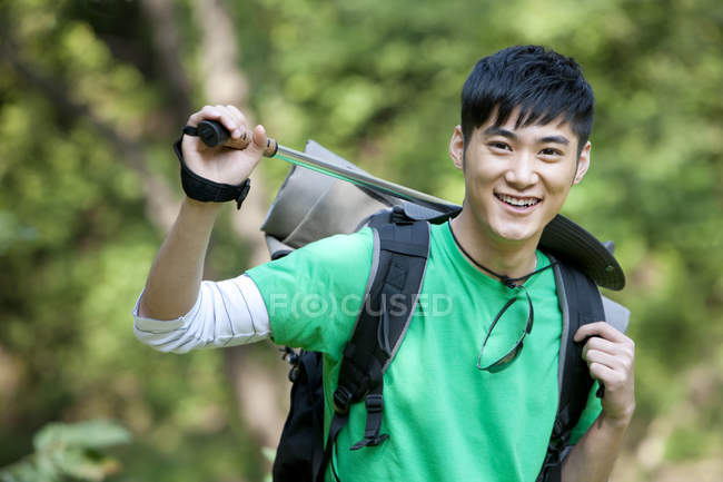 Chinese male backpacker with hiking pole in forest — Stock Photo