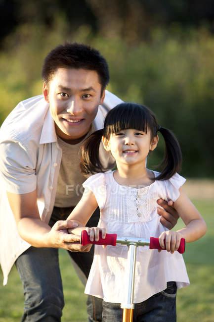 Китайский отец учит дочь кататься на скутере — стоковое фото