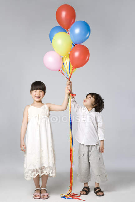 Chinese children holding multi-colored balloons on gray background — Stock Photo
