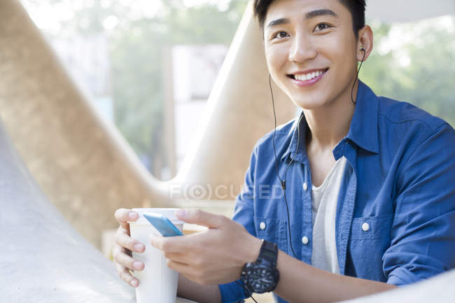 Chinese man listening to music with smartphone and holding coffee — Stock Photo