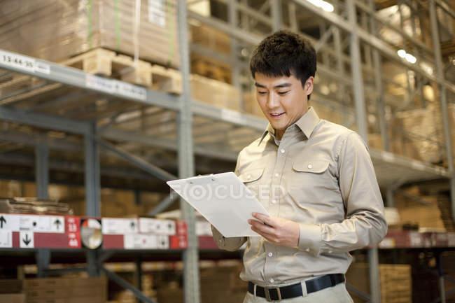 Trabajador almacén chino masculino con portapapeles - foto de stock