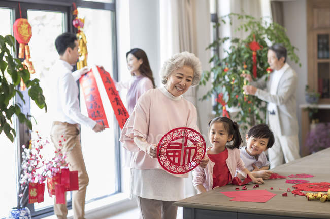 Cheerful family decorating home for Chinese New Year — Stock Photo