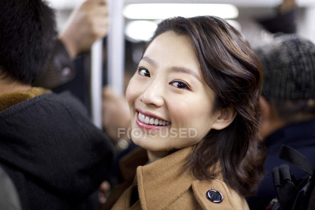 Mulher chinesa alegre no trem do metrô — Fotografia de Stock
