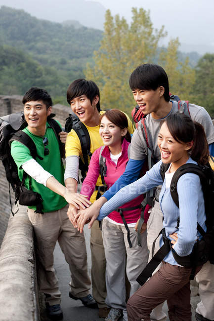 Chinese hikers stacking hands and posing on Great Wall — Stock Photo