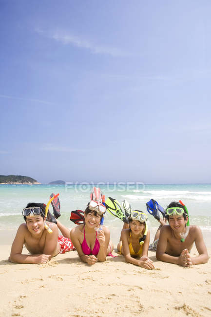 Chinese friends lying with scuba masks at beach sand — Stock Photo